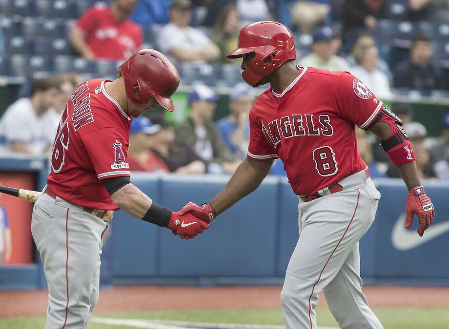 The Angels' Justin Upton (8) is greeted by Kole Calhoun after homering in his return to action. Photo: Fred Thornhill / Associated Press