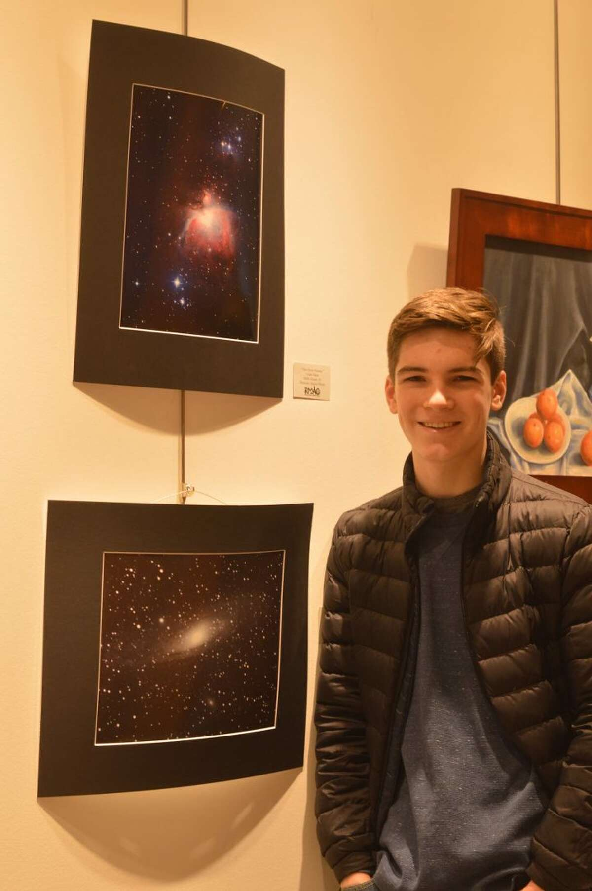 """Ridgefield High School sophomore Grant Yaun stands with his piece """"The Orion Nebula"""" in the Ridgefield Library."""