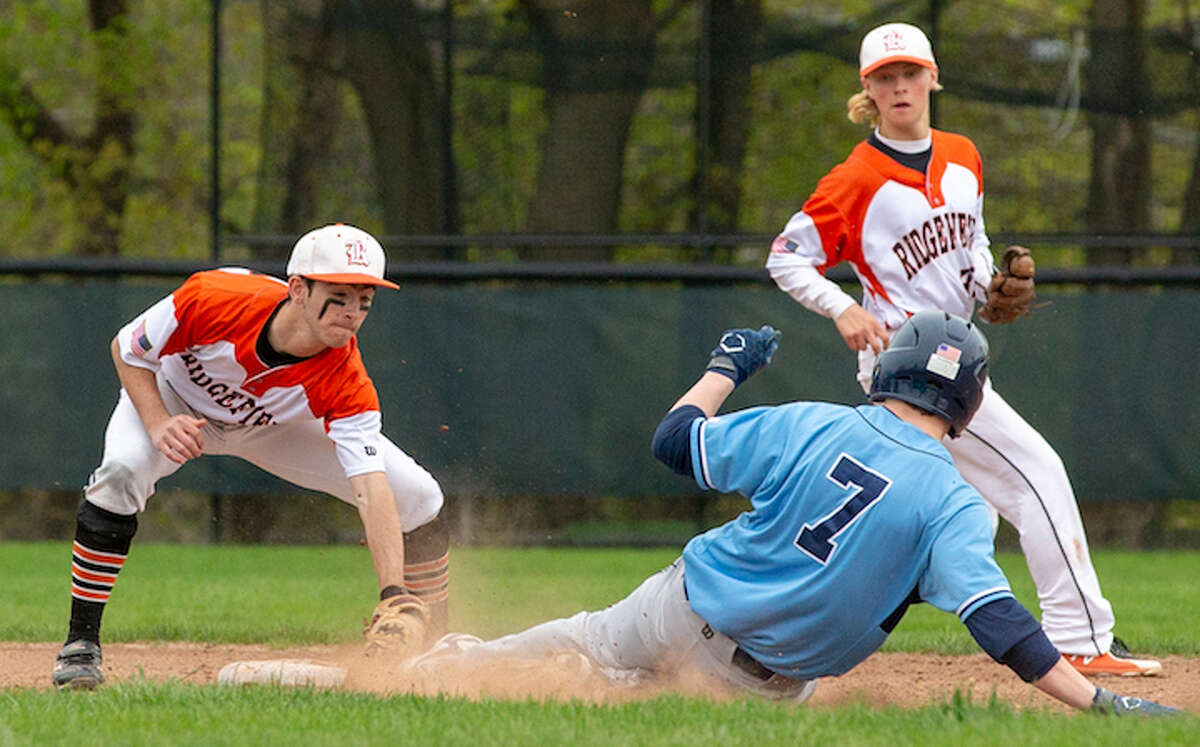 Bobby Arent puts the tag on Wilton's Kyle Phillips during Monday's baseball game. Backing up the play is Ridgefield shortstop Colin LaCoille. - GretchenMcMahonPhotography.com