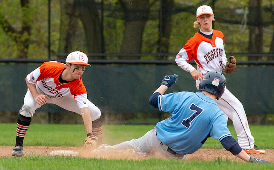 Bobby Arent puts the tag on Wilton's Kyle Phillips during Monday's baseball game. Backing up the play is Ridgefield shortstop Colin LaCoille. — GretchenMcMahonPhotography.com