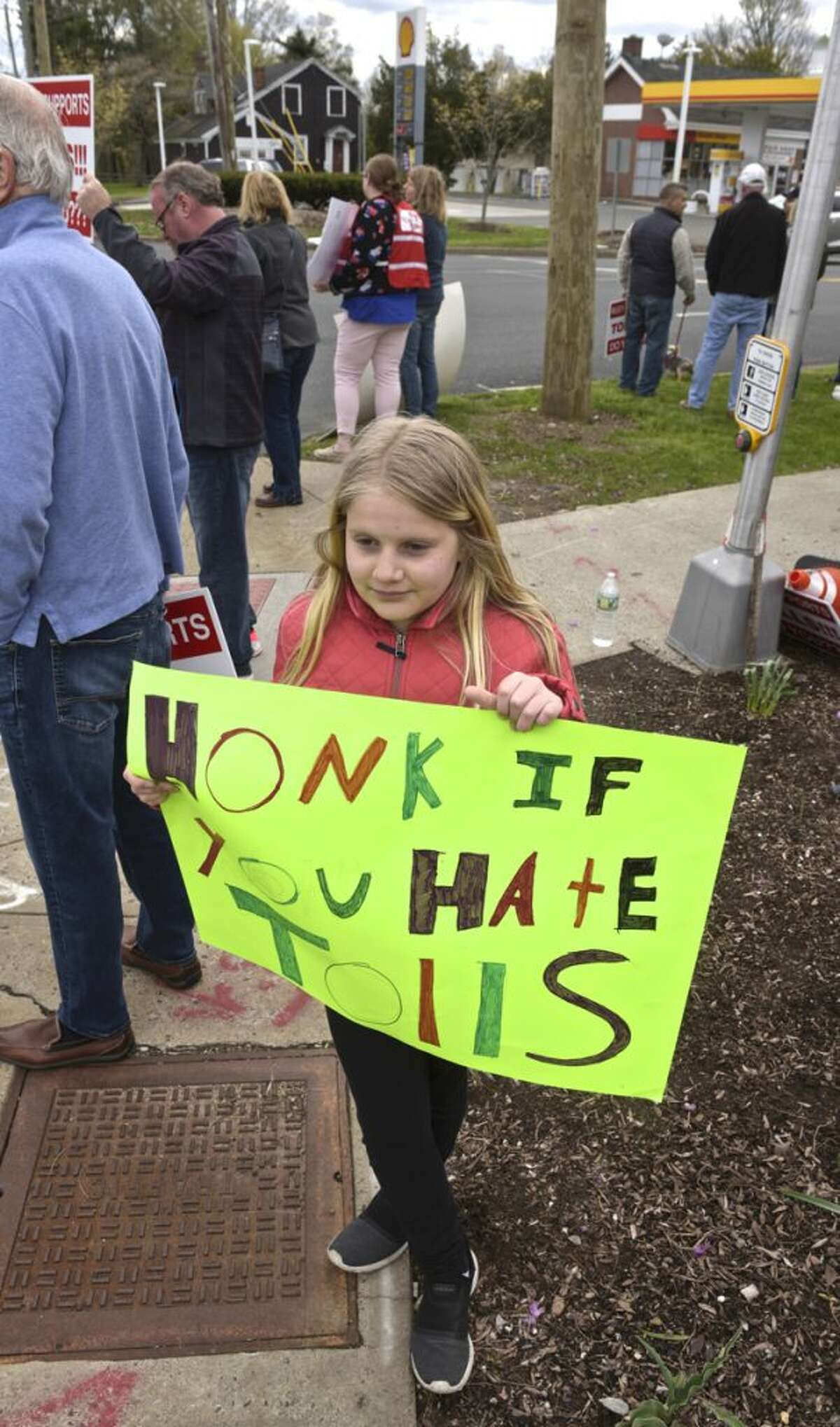 Rachel Floegel, 11, of Ridgefield, takes part in a No Tolls Ct protest in front of Copps Hill Plaza, on Danbury Road, in Ridgefield, Conn., Saturday morning, April 27, 2019.