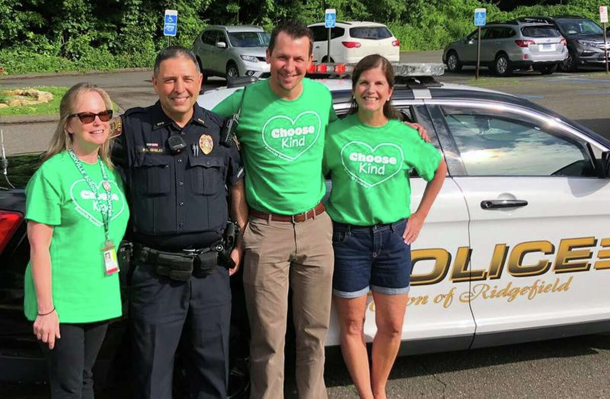 Branchville Elementary School Mary Nyland won the school's silent auction on June 19. Nyland and co-worker Laurie Bellagamba got a ride to school by Ridgefield police officer Mark Giglio on the last day of school. Also in the picture is principal Keith Margolus, middle.