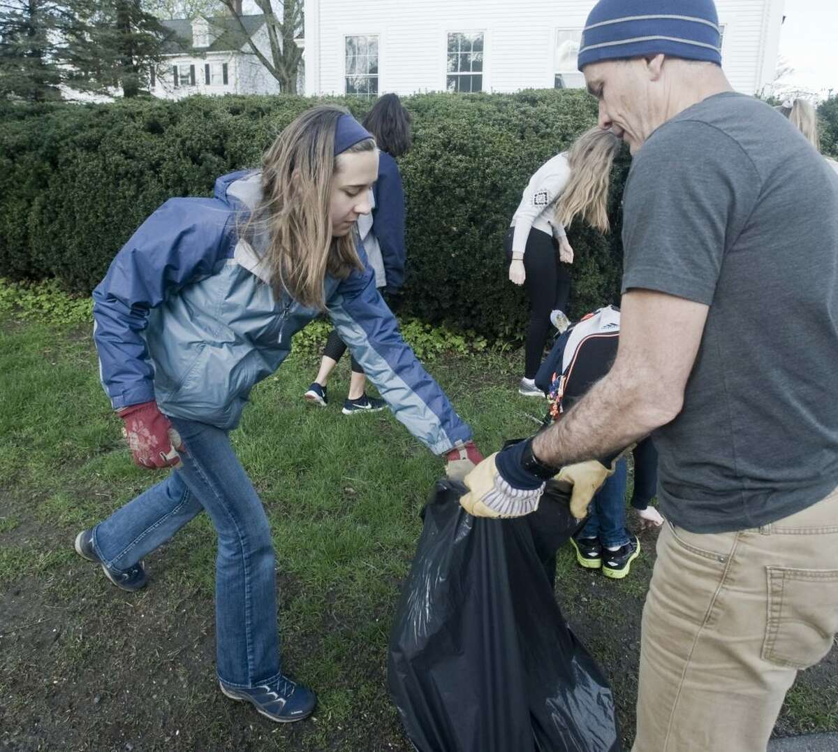 Ninth-grader Della Finchan puts collected garbage in the bag held by Sean Hogan. Finchan and Hogan picked up trash in front of St. Stephen Church on Main Street. - Scott Mullin photo