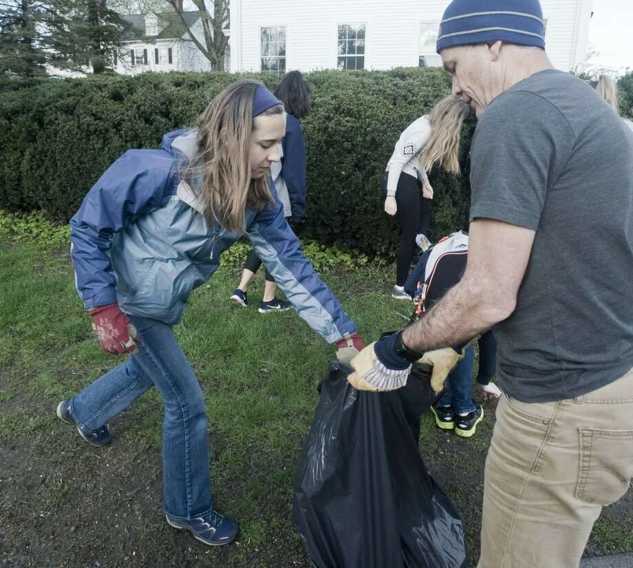 Ninth-grader Della Finchan puts collected garbage in the bag held by Sean Hogan. Finchan and Hogan picked up trash in front of St. Stephen Church on Main Street. — Scott Mullin photo