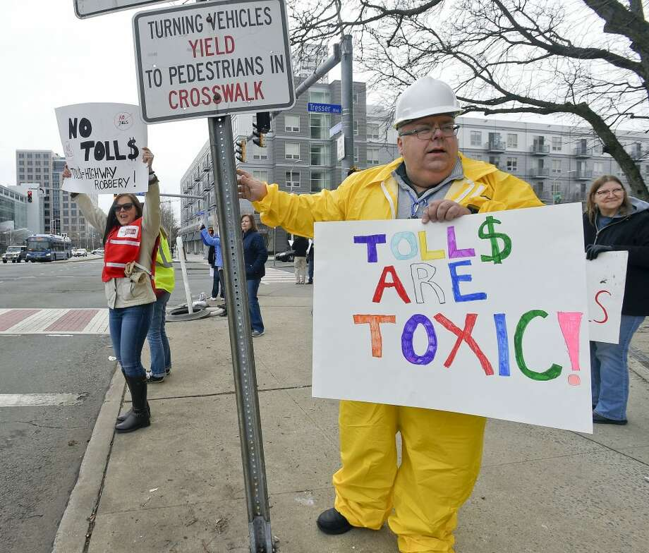 At right, Mike Johnson of New Canaan joins with others from the anti-toll group No Tolls CT, as they stage a protest in front of the Government Center on Saturday, Feb. 23, 2019 in Stamford, Connecticut.