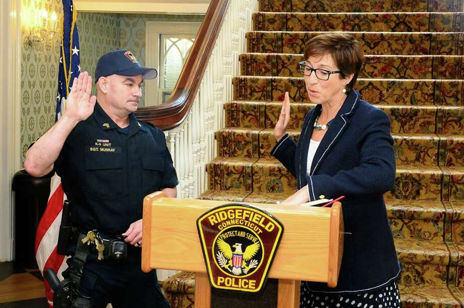 Ridgefield police officer Shawn Murray is sworn in as a sergeant by Town Clerk Wendy Lionetti Wednesday, April 16, at the Lounsbury House.