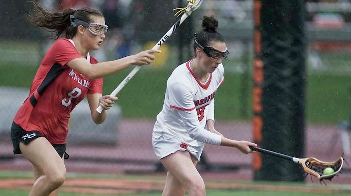 Hannah Boylan keeps the ball away from New Canaan's Katelyn Sparks during Monday's game. - Scott Mullin photo