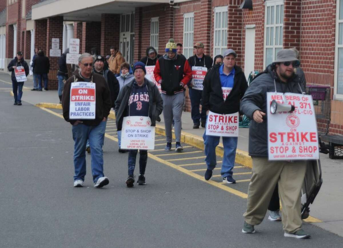 Striking grocery workers marched on the sidewalk in front of RIdgefield's Stop and Shop store Thursday. Customers could go in and out, although relatively few chose to cross the picket line.