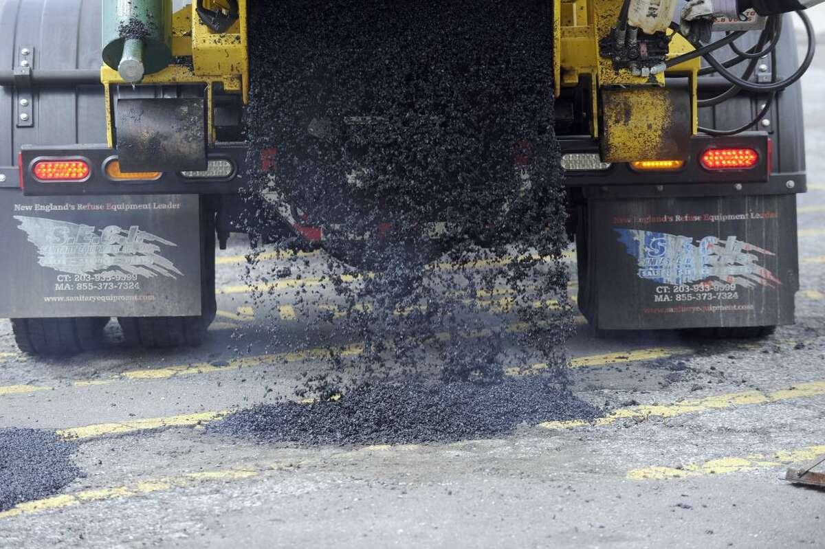 Hot patch asphalt material fills a pothole on Thursday, April 11, 2019.