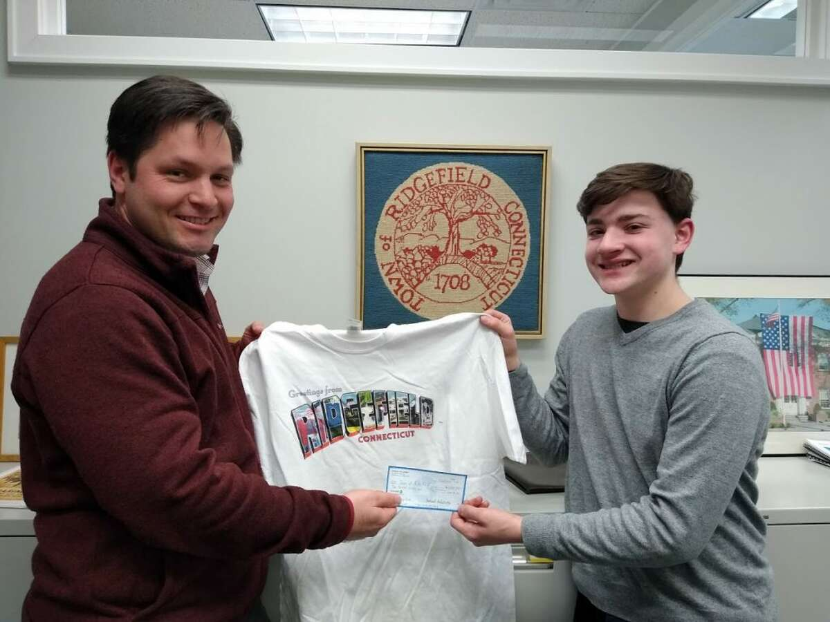 Tony Phillips, the town's director of Social Services, receives a donation check from Ridgefield High School junior Sam Sulzinsky.