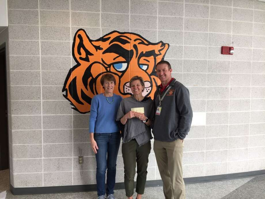 RTS treasurer Carol Gardell, left, presents a check for a new scoreboard project to Jill Bornstein president of Tiger Hollow Inc, and Dane Street, Ridgefield High School Athletic Director.