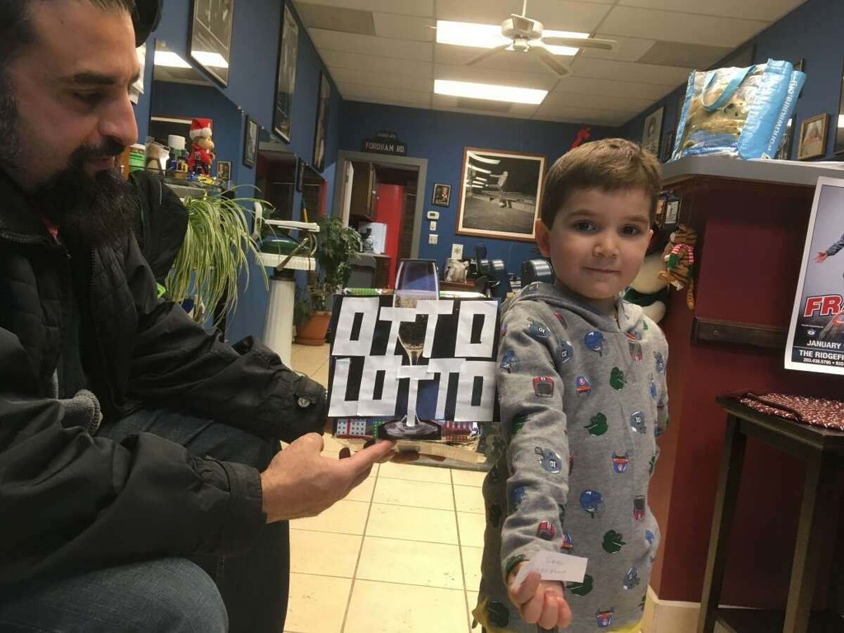Otto's Lotto, an annual game run each year for the past 38 years by longtime Ridgefield barbershop Otto II Barbershop at 113 Danbury Road, awarded four free haircuts to customers who put their names into a hat over the Thanksgiving and Christmas holidays.Pictured here is Otto's grandson Daniel Pacella, 4, drawing one of the lotto's tickets. The shop's owner, Otto Muraca, has been cutting hair for 53 years.