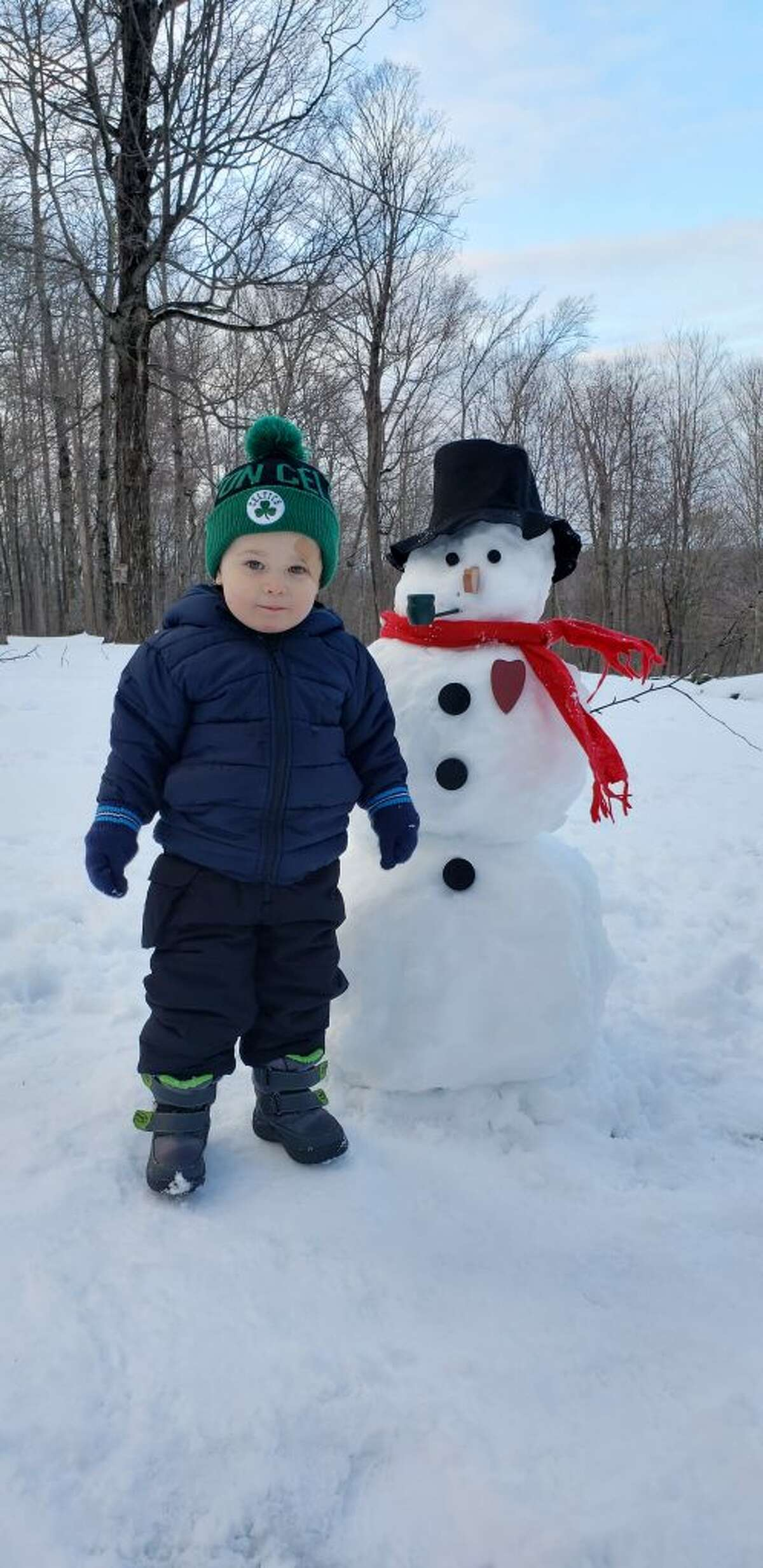 Jack Rowe, 2, and with his snowman friend.