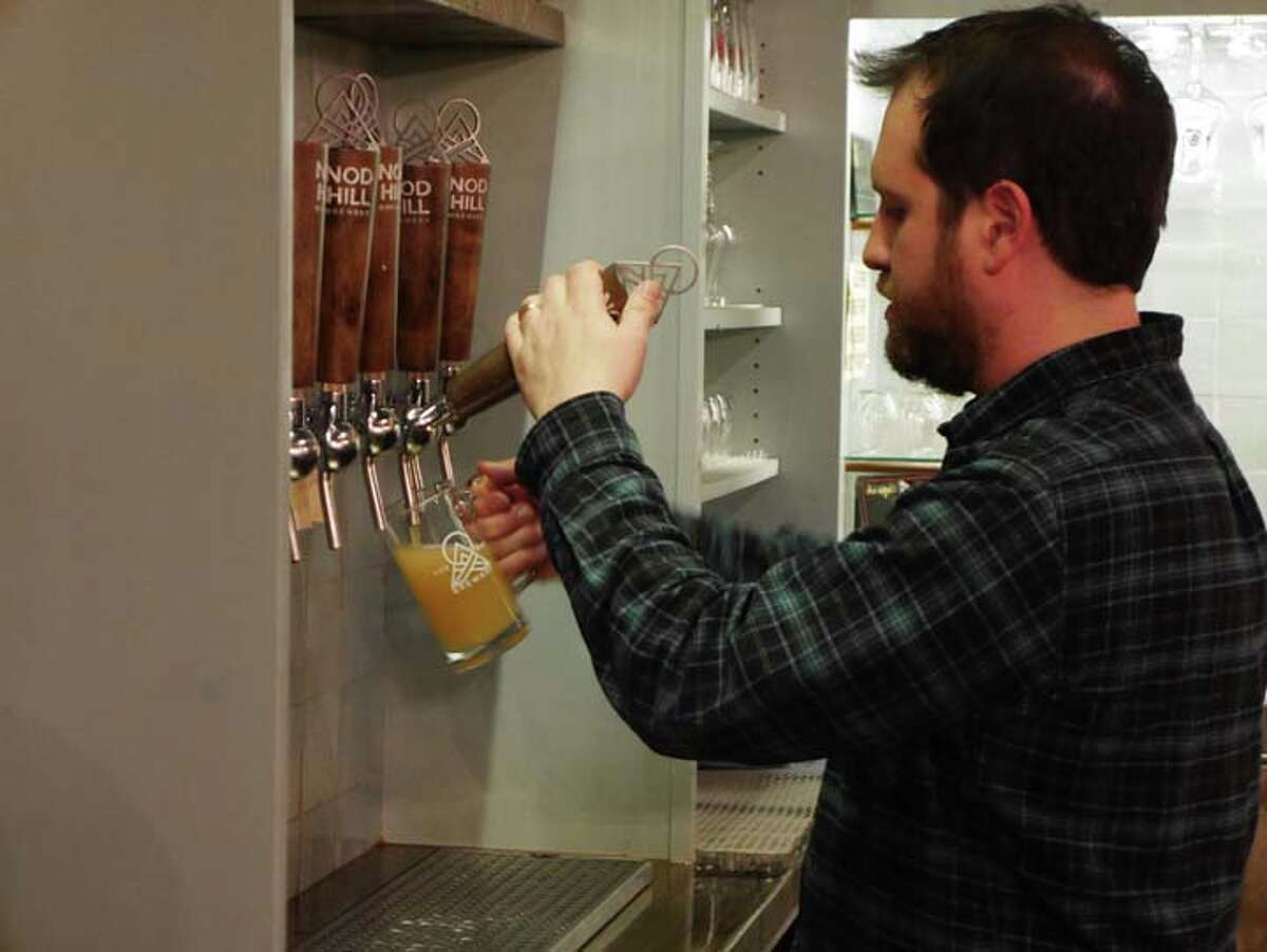 Parkinson's research on tap - Nod Hill Brewery co-owner David Kaye pours a glass of beer during the Pints for Parkinson's fundraiser, Feb. 27. The event raised funds for research through the Michael J. Fox foundation.