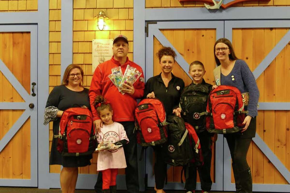 Family and Children's in Aid in Danbury received a generous donation of 30 backpacks and 30 toothbrush kits from the Max Michael Rosenfield Foundation last week. Pictured, from left to right: Allison Carballo, development director of Family and Children's Aid; Margo, Ken, Jill and Adam Rosenfield; and Ridgefield High School senior Bridget Kager. Kager has been collecting backpacks and making blankets through her Girl Scout Gold Award project, and donating them to Family and Children's Aid. The Max Michael Rosenfield Foundation made its donation to her cause through baseball clinic funs that helped pay for the backpacks. - Steve Coulter photo