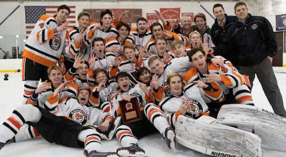 The Ridgefield High boys hockey team celebrates its third straight FCIAC title after beating Greenwich, 8-1, on Saturday. Photo: John McCreary / For Hearst Connecticut Media