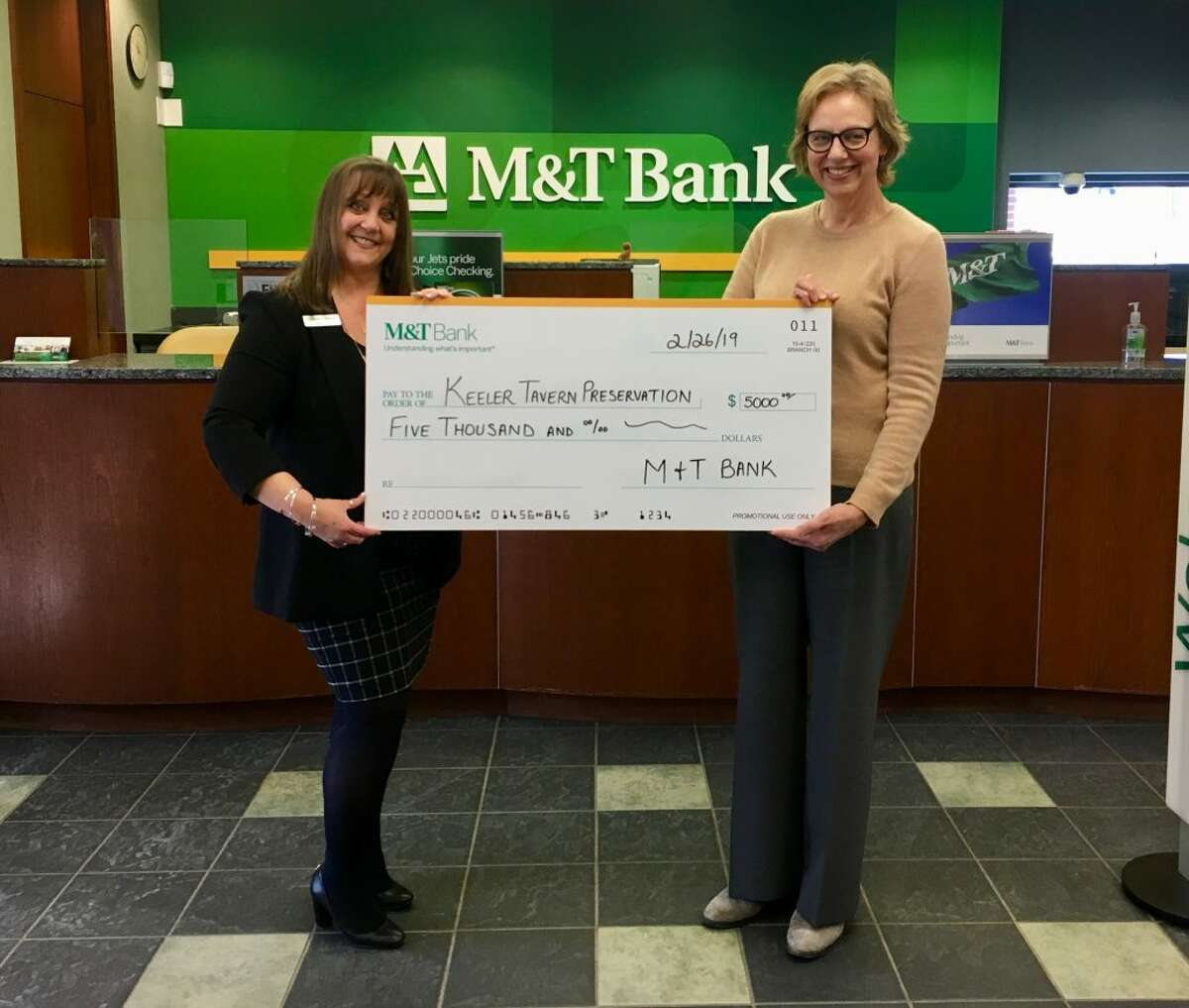 Colleen Caranfa, manager at M&T Bank's Ridgefield branch, and Hildi Grob, Keeler Tavern Museum and History Center's executive director, hold a $5,000 facsimile check representing the grant that the Museum recently received from M and T Bank for visitor research.