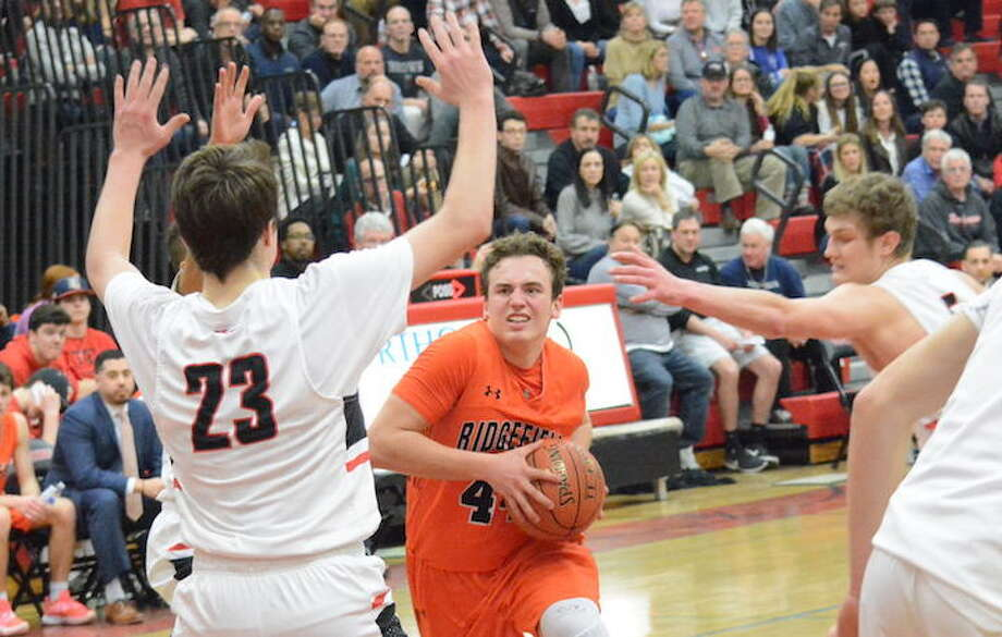 Chris Knachel drives to the basket during Ridgefield's win over New Canaan in the FCIAC quarterfinals. — Andy Hutchison photo