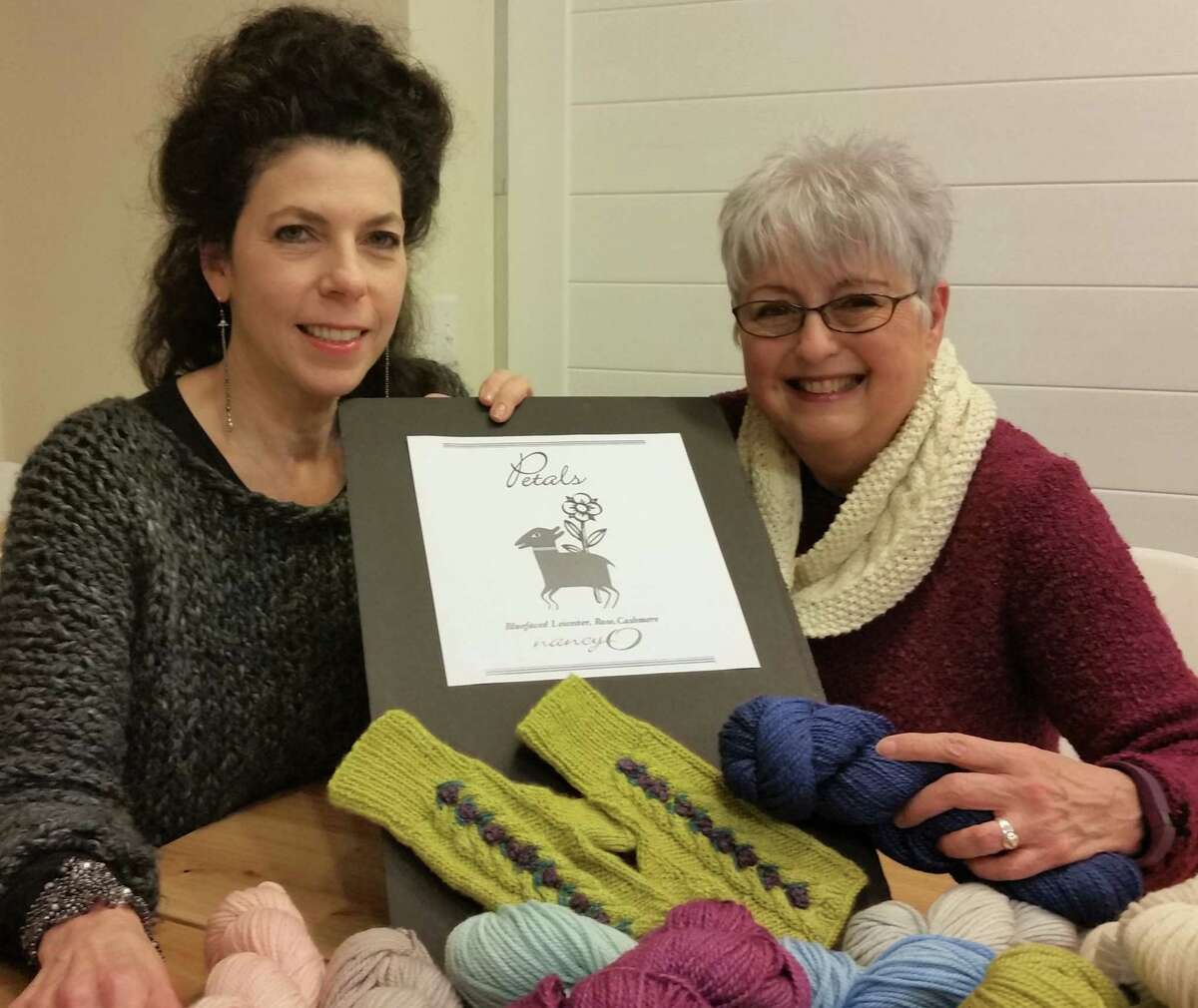 Nancy O'Connell, right, owner of nancy O, with Ridgefield artist Amy Bock, who designed the labels for the nancy O private-label yarns. Shown is a replica of the label for one of the two new yarns.