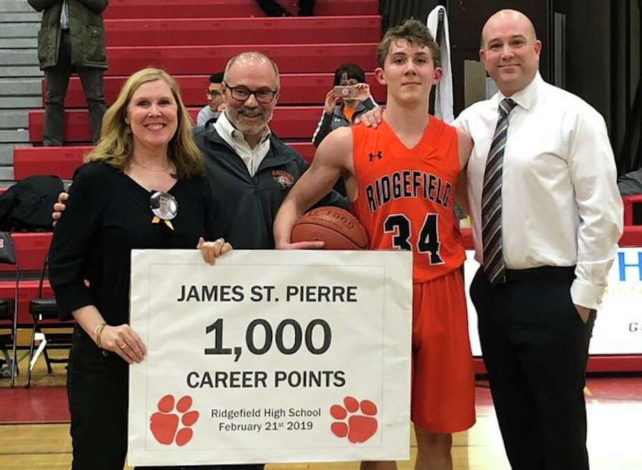 James St. Pierre was honored after scoring his 1,000th career point during Ridgefield's game at Fairfield Warde. St. Pierre is shown with his parents and Ridgefield head coach Andrew McClellan (far right). — Contributed photo