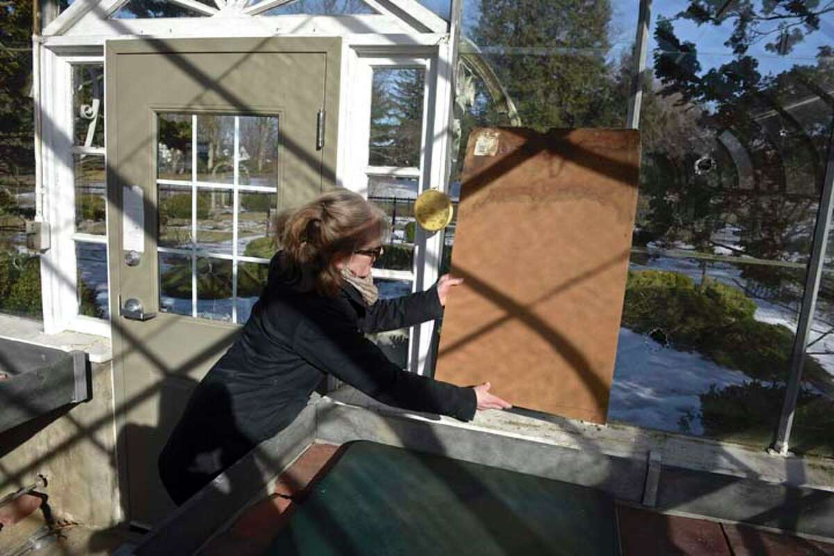 Terry McManus, of Ridgefield and a member of the Ridgefield Garden Club/Garden Conservation and Trust, covers holes in the windows of the Ballard Park greenhouse, a Lord & Burnham greenhouse. It was built by Mrs. Ballard's father, Lucius Bigelow in 1906. Tuesday, February 19, 2019, in Ridgefield, Conn.