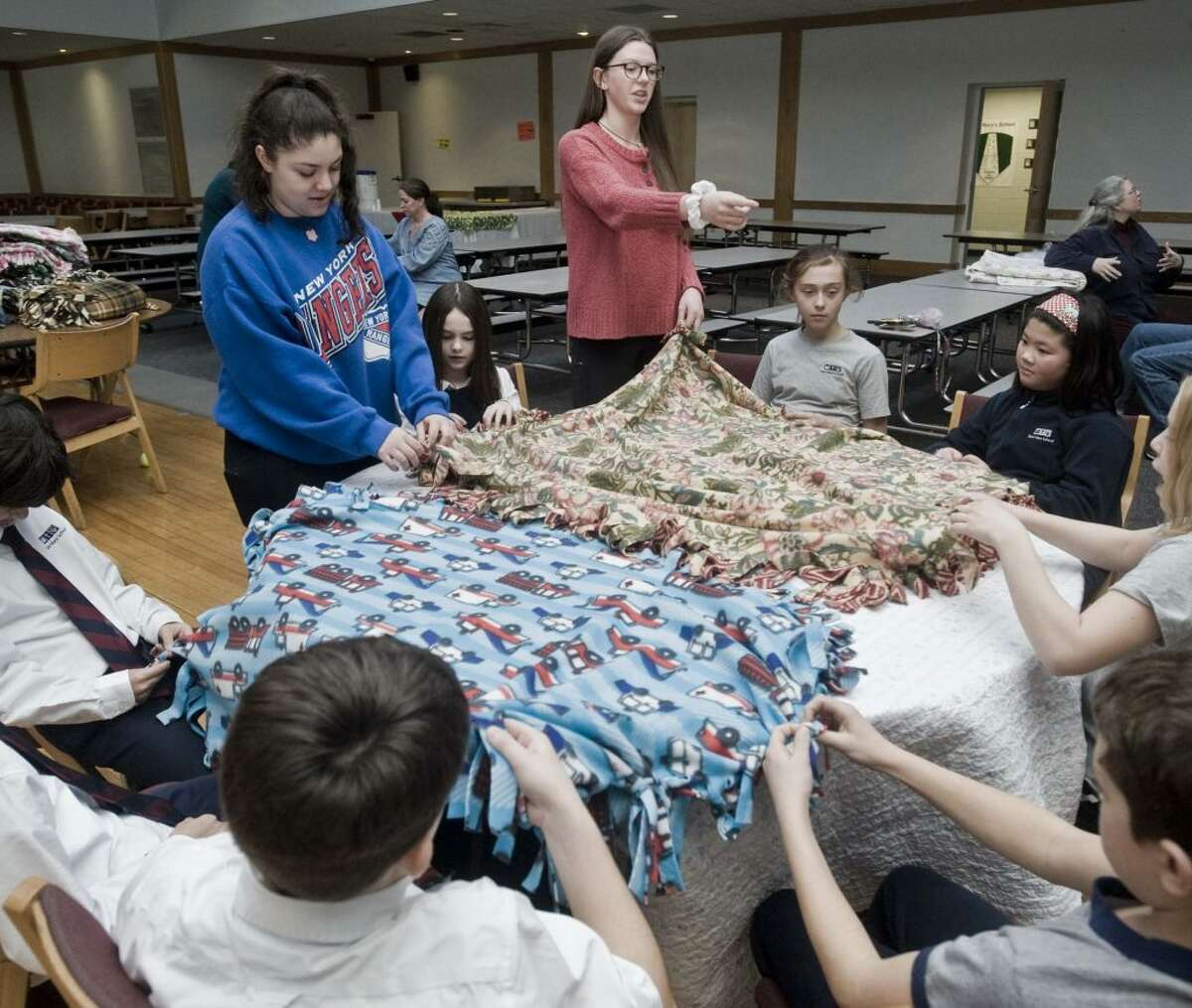 Ridgefield High School senior Bridget Kager, red shirt, works on blankets with Keleigh Zuckert, blue shirt, a senior at Immaculate High School, on Feb. 6 at St. Mary's. The high schoolers were helped by fourth and fifth grade students from Saint Mary's School. Kager, a member of Girl Scout Troop 50123, is making blankets and collecting backpacks for Family and Children's Aid in Danbury as part of her Gold Award project. - Scott Mullin/Hearst Connecticut Media