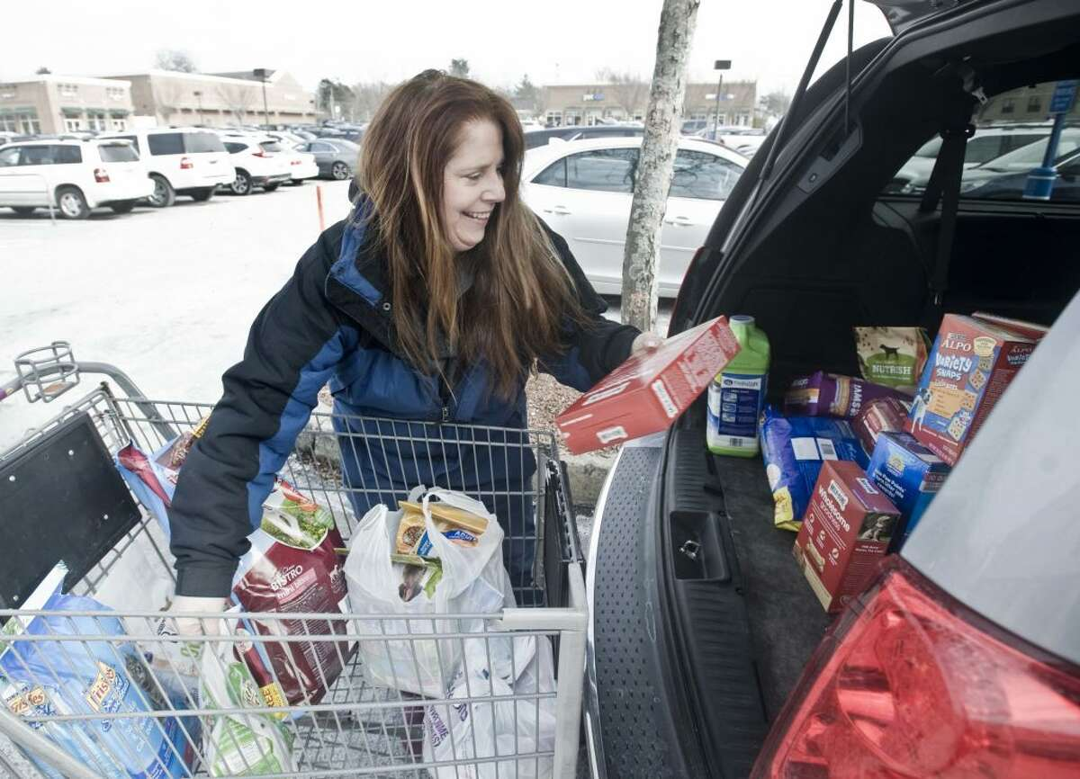 "ROAR Executive Director Kerry Dobson loads the ""Stuff a Van"" with donated pet food. - Scott Mullin photo"