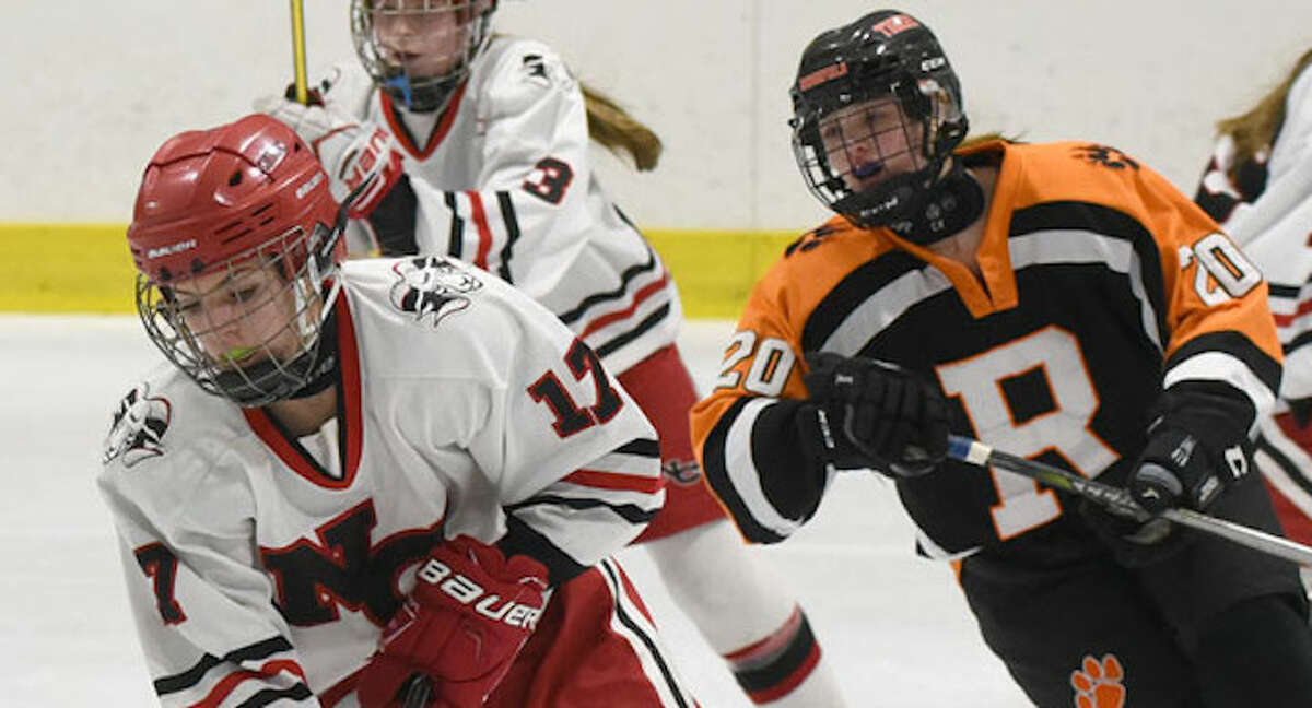New Canaan's Sadie Frame controls the puck in the neutral zone, as Ridgefield/Danbury's Rebecca Gartner chases during a girls hockey game at the Darien Ice House on Monday, Jan. 28. - Dave Stewart/Hearst Connecticut Media photo