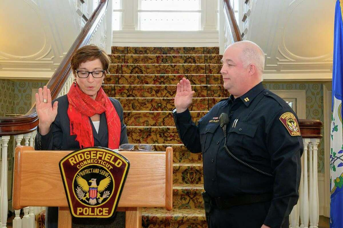 Lt. Shawn Platt of the Ridgefield Police Department is sworn in as captain by Town Clerk Wendy Lionetti during a ceremony at Lounsbury House Thursday, Jan. 17.