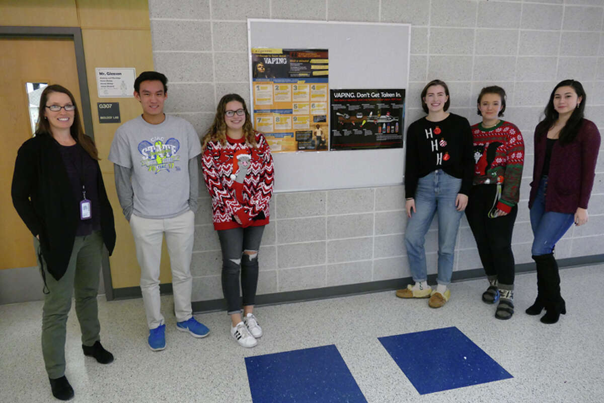 From left to right: Ridgefield High School health teacher Margaret Meriwether stands with seniors Tadd Long, Danielle Butz, Anna Doman, Nikki Rdzanek and Jessica Fine in front of one of the school's anti-vaping posters. The students have been working to combat vaping through creating public service announcements that are posted and shown around the school. - Peter Yankowski photo