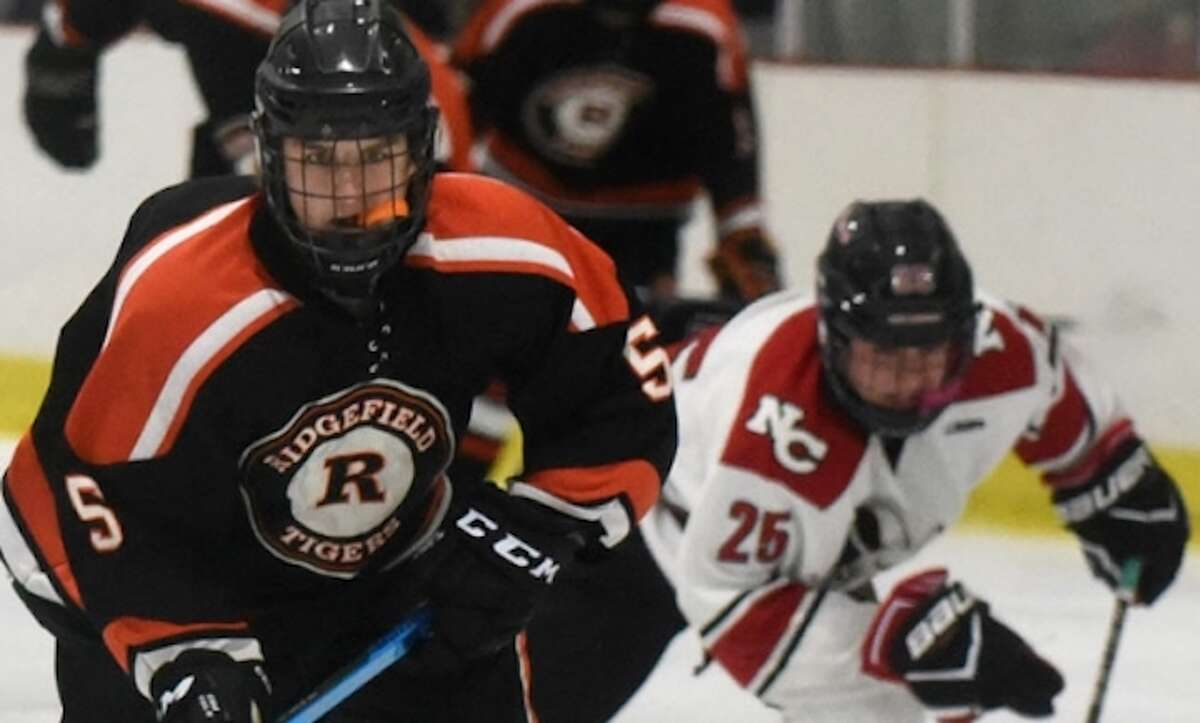 Henry Garlick skates past a New Canaan player during Ridgefield's 6-1 win Tuesday night. - Dave Stewart photo