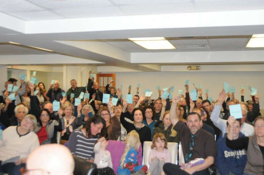 Voters demonstrate approval for a proposed ban on fracking waste Wednesday night in the lower level conference room of town hall. — Macklin Reid photo
