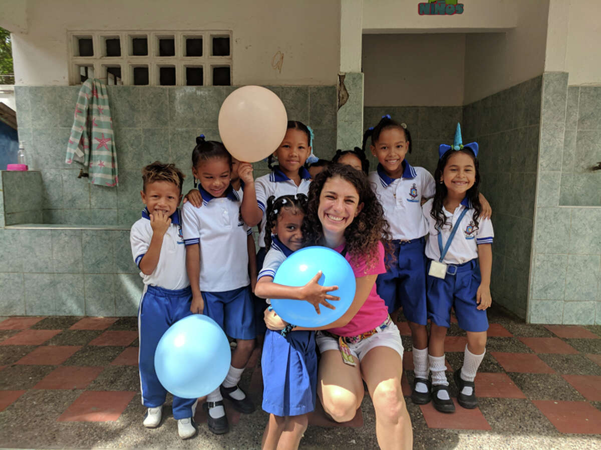 Ridgefield resident Carrie Smuckler smiles with children at La Boquilla, a preschool outside of Cartagena.