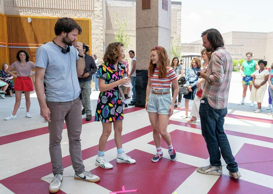 See all the Stranger Things season 3 photos                 Stranger Things returns for its third season on Netflix on July 4, with some new faces and new settings. We'll share both episodic and behind-the-scenes photos here, updating as new images are released.Here, show co-creator Ross Duffer, actresses Millie Bobby Brown (Eleven) and Sadie Sink (Max), and co-creator Matt Duffer stand at what might be Starcourt Mall, which will feature prominently in the new season. Photo: CBSI/CNET