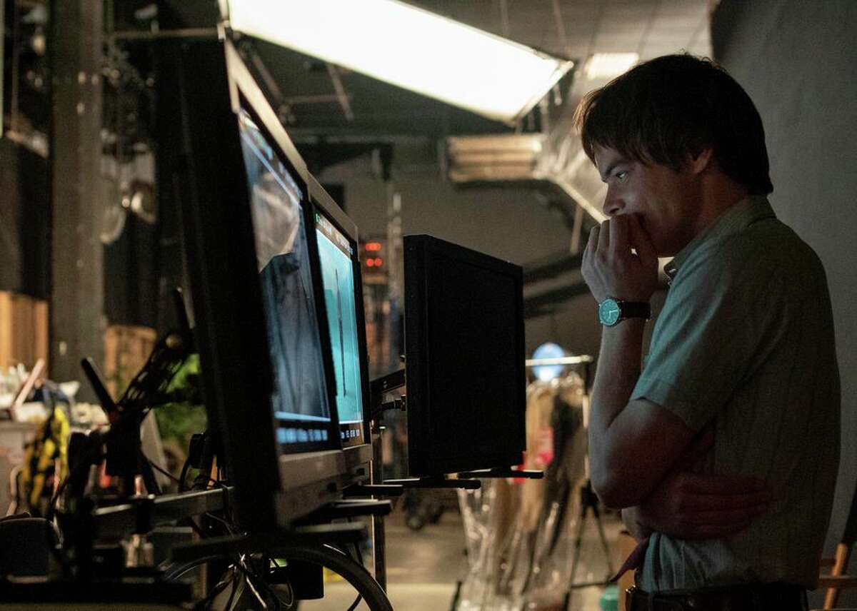 Charlie Heaton (Jonathan) looks at a computer monitor in a behind-the-scenes clip.