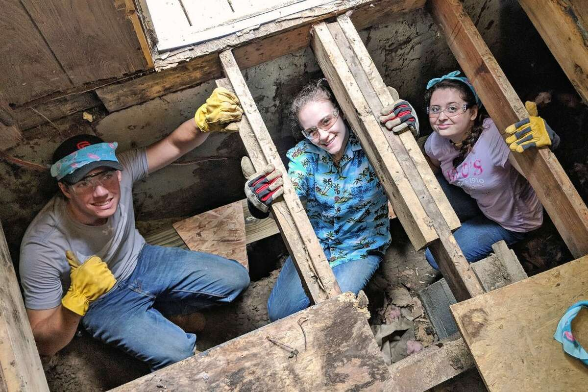From left: Alec Pool, Ashley Welter and Kiera McCrohan, all of Ridgefield, work below the joists as they replace the floor of a home during Jesse Lee Appalachia Service Project's mission trip last summer in Leslie County, Ky.