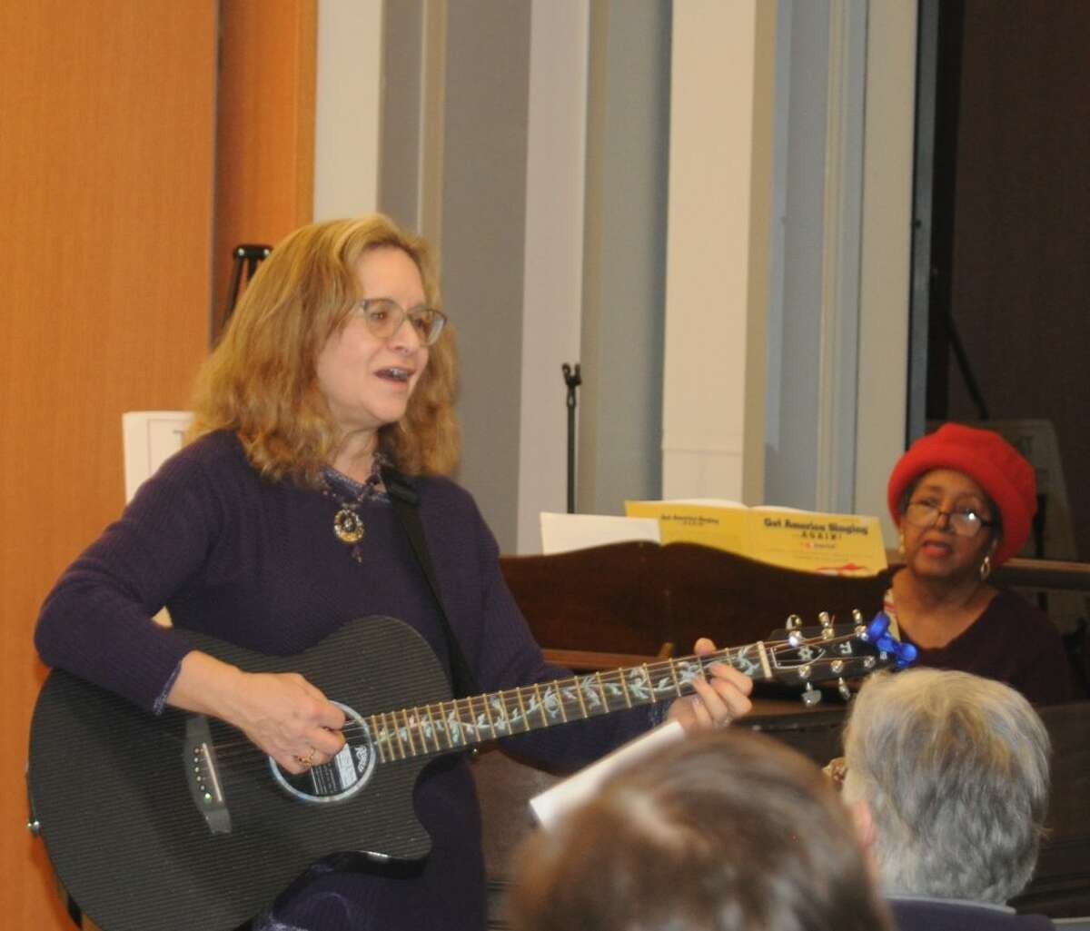 With Deborah Katchko-Gray on guitar and leading the vocals, and Gigi Van Dyke on piano, about 20 people who showed up at the Ridgefield Library had all the musical leadership they needed for a room-rocking community sing-along on Sunday, Dec. 16. Folks joined voices on songs ranging from The Beatles to Billy Joel to standards like Take Me Out to the Ballgame and Woody Guthrie's This Land is Your Land. Katchko-Gray, the cantor of Congregation Shir Shalom, has been organizing community sing-alongs for a couple of years now. The next one is Jan. 6 from 3:30 to 5 at the library. Songbooks with the words are provided, guitars and other instruments are welcome. - Macklin Reid photo