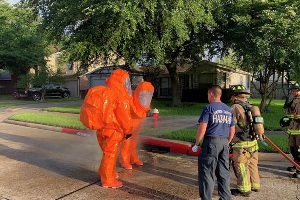 Firefighters wash down Harris County Fire Marshal's Office hazmat team members after a chlorine leak at a community pool in Atascocita on Tuesday, June 18, 2019.