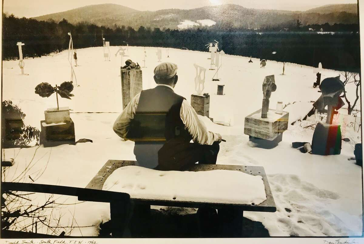 Photographer David Budnick took this image in 1962 of sculptor David Smith overlooking his field of steel sculptures in the winter of 1962 on Smith's Tick Ridge Farm above Lake George in Bolton Landing
