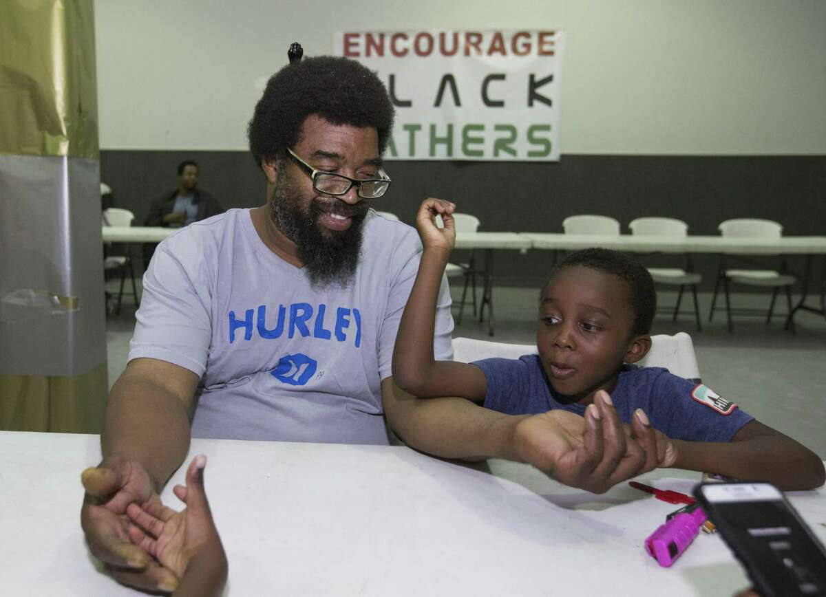 Eric King, 50, plays with his sons, Vincent King, 6, and Eric King Jr., 7, not in photograph, at the 6th annual Day of Enouragement for black fathers at SHAPE Community Center on Sunday, June 16, 2019, in Houston. Activist Deric Muhammad hosts this annual event to combat the stigma of black fathers not being around their children.
