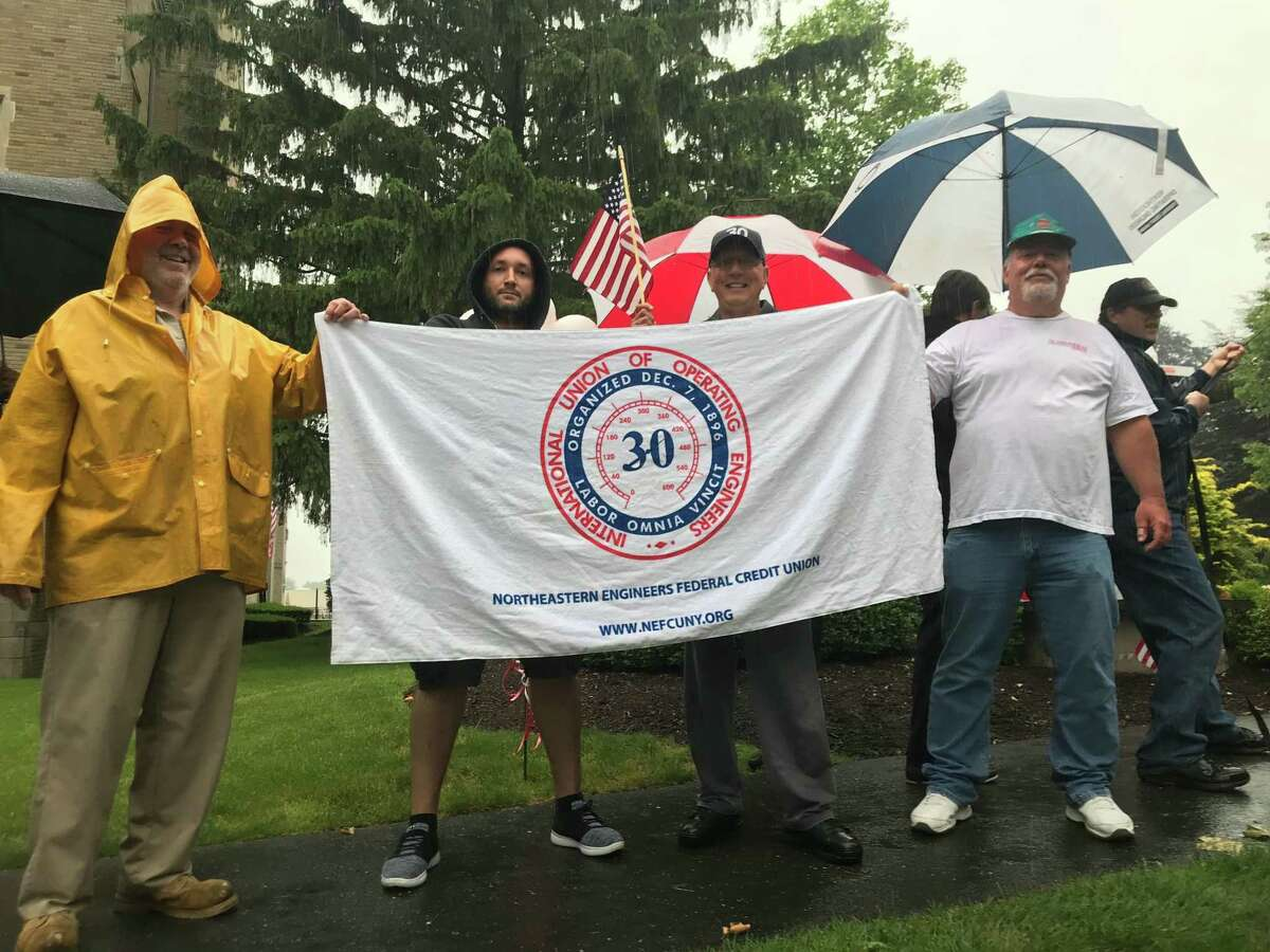 Fairfield University employees held an International Union of Operating Engineers banner as they demanded union health care.