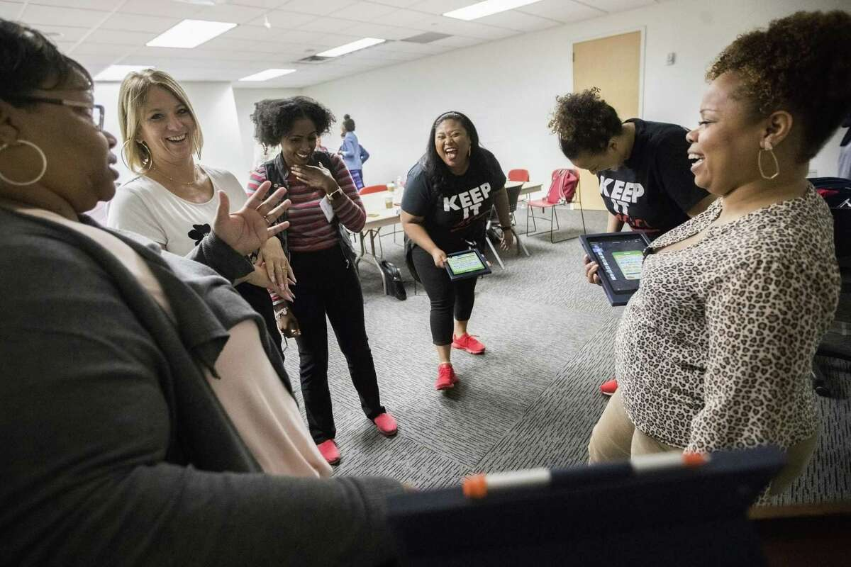 LaTonya Martin, Tiffany Fondal, and Amber Byars share a moment while leaning about computer apps interactivity at the Houston Community College on Friday, June 14, 2019, in Houston. Area teachers got code training from Apple instructors so they can have improved tools to teach their students.