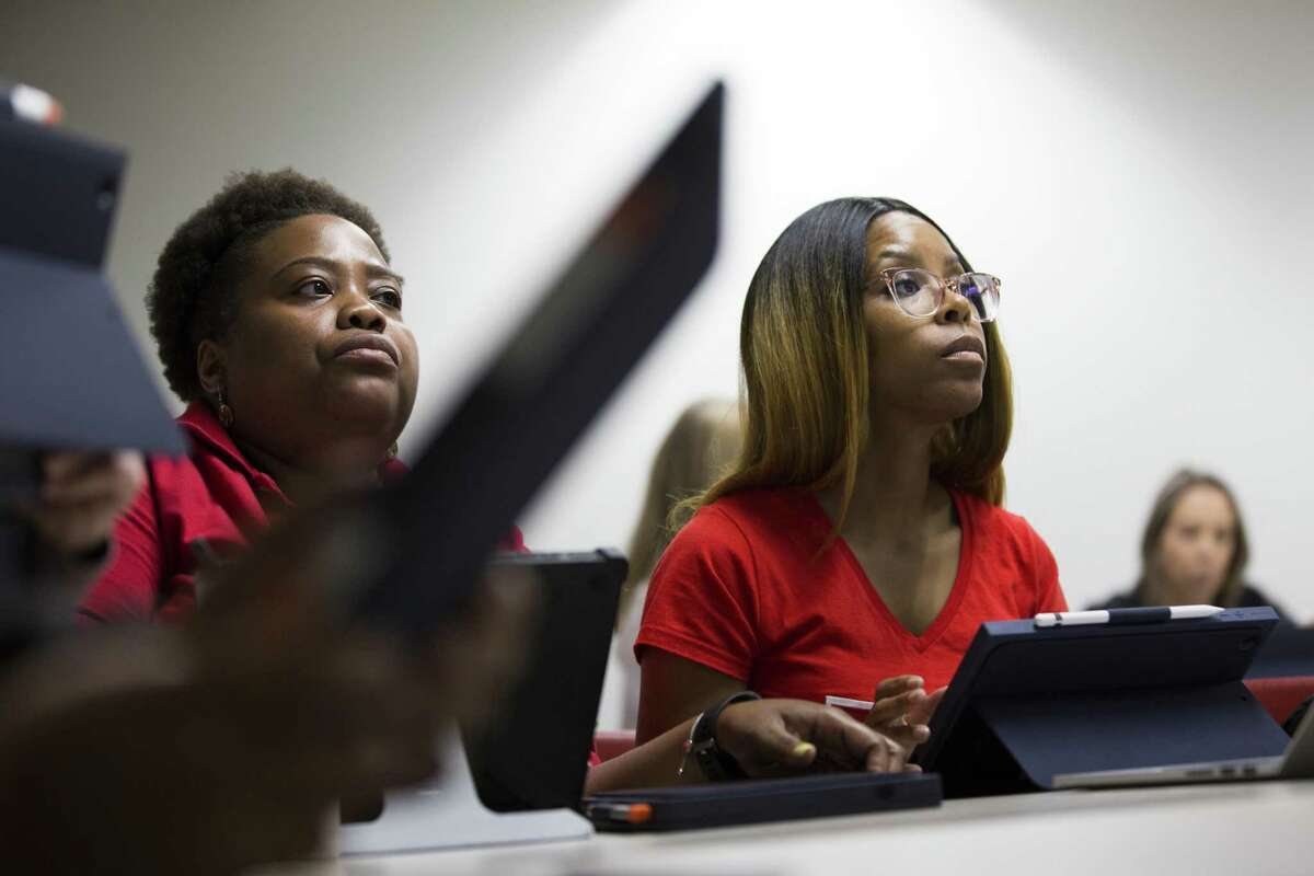 Lesley Ayers-Barnes and Jasmi Brown listen to their instructor during coding and apps class between a partnership between the Houston Community College and Apple on Friday, June 14, 2019, in Houston.