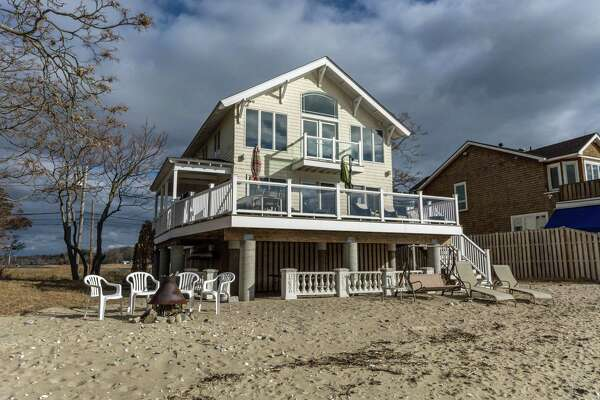 The six-room waterfront contemporary colonial house at 56 Compo Mill Cove in the Compo Beach neighborhood has a private sandy beach and water views.