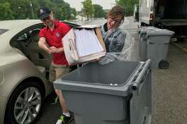 Rep. Katie Stuart helps transfer a box of old documents to a secure transport container to be shredded.
