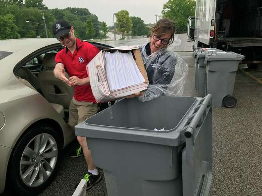 Rep. Katie Stuart helps transfer a box of old documents to a secure transport container to be shredded. Photo: For The Intelligencer