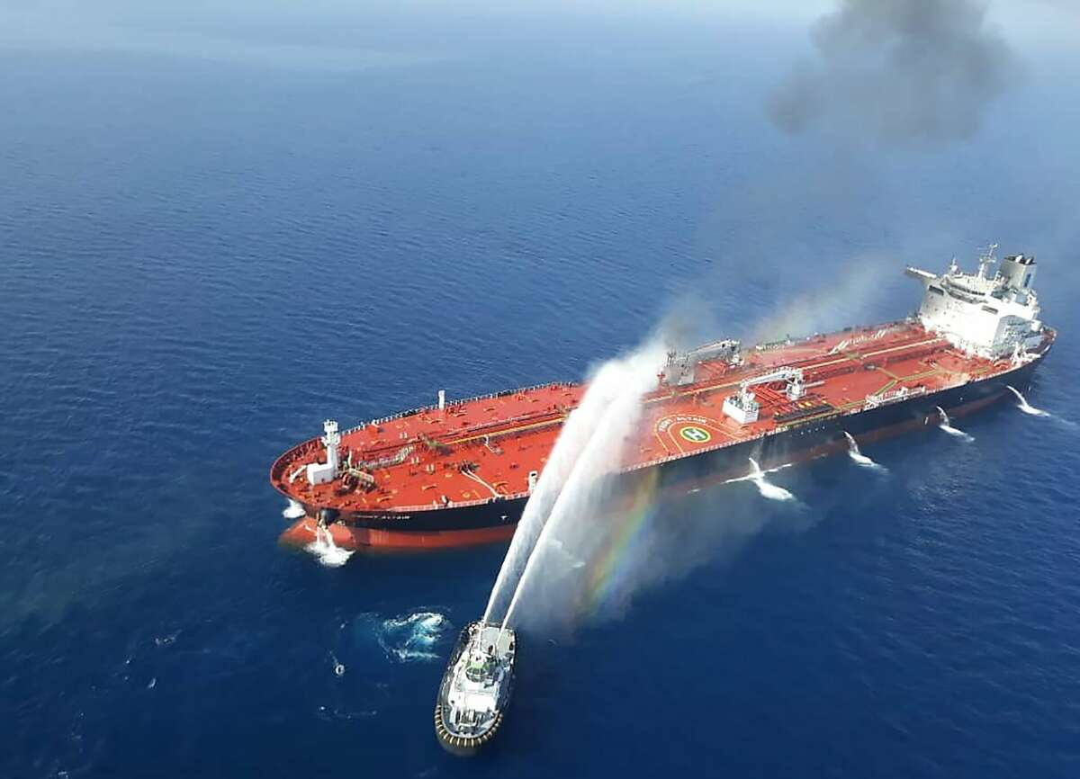 (FILES) In this file picture obtained by AFP from Iranian news agency Tasnim on June 13, 2019 reportedly shows an Iranian navy boat trying to control fire from Norwegian owned Front Altair tanker said to have been attacked in the waters of the Gulf of Oman. - President Donald Trump downplayed recent attacks on oil tankers in the Gulf of Oman that Washington blames on Iran and noted that the United States is less dependent on energy supplies from the region.