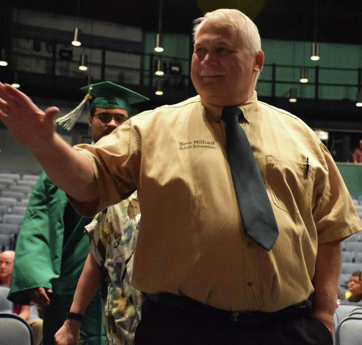 Spectrum/New Milford Adult Education held commencement exercises June 12, 2019 for 27 graduates. The ceremony was held at New Milford High School and included the presentation of student speeches, and the presentation of awards and diplomas. Above, Guidance Counselor Joe Neff, who marked his 20th year in that role this year, waves to family members at the ceremony.