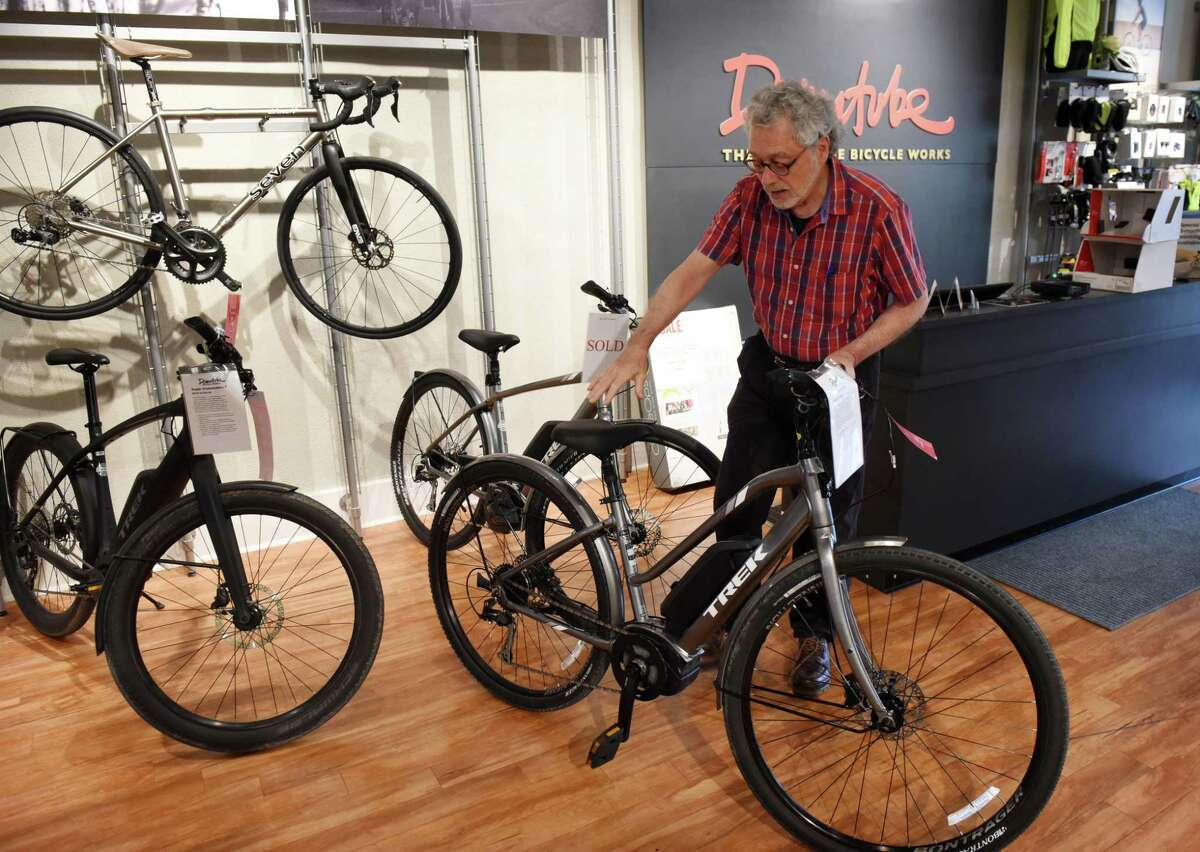 Robert Fullem, owner of The Downtube Bicycle Works, displays an e-bike from Trek, which he sells at his Madison Avenue shop on Tuesday, June 18, 2019, in Albany, N.Y. The bike uses a battery-powered pedal assistance system. (Will Waldron/Times Union)