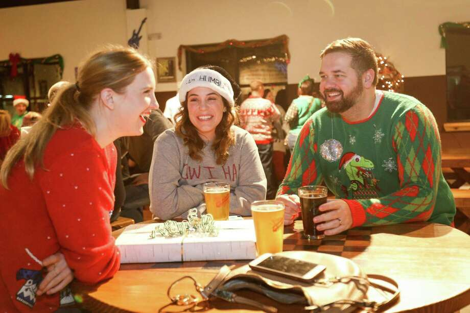 The Woodlands residents Lindsey Schulz, left, and Sarah and Jeff Wilkins chat while donning ugly Christmas sweaters for a contest during the Southern Star Christmas Party on Friday, Dec. 22, 2017, at the Southern Star Brewing Company in Conroe. Photo: Michael Minasi, Staff Photographer / Houston Chronicle / © 2017 Houston Chronicle